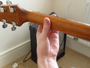 holding the guitar neck - rear view